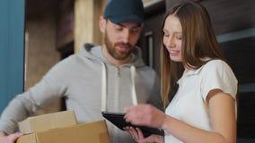 Levering, post, mensen en het verschepen concept - gelukkige mens die pakketdozen leveren aan klantenhuis Het geven van klembord  stock videobeelden