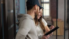 Levering, post, mensen en het verschepen concept - gelukkige mens die pakketdozen leveren aan klantenhuis Het geven van klembord  stock footage