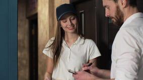 Levering, post, mensen en het verschepen concept - gelukkige vrouw die pakketdozen levert aan klantenhuis Het geven van klembord  stock videobeelden