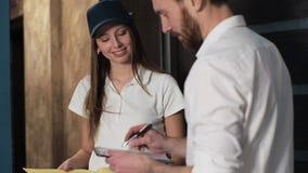 Levering, post, mensen en het verschepen concept - gelukkige vrouw die pakketdozen levert aan klantenhuis Het geven van klembord  stock footage