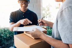 Leverings jonge mens die zich bij de deur van huis en dragende pakketten voor jong mannetje aan het ondertekenen bevinden royalty-vrije stock afbeeldingen