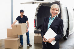 Leveringsbestuurder die zijn bestelwagen met manager het glimlachen inpakken royalty-vrije stock foto