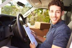 Leveringsbestuurder Sitting In Van Filling Out Paperwork stock foto's