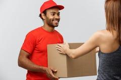Leveringsconcept - Knappe Afrikaanse Amerikaanse leveringsmens die pakket geven aan huiseigenaar Geïsoleerd op Grijze studi royalty-vrije stock foto's