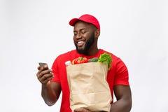 Leveringsconcept - Portret van de Knappe Afrikaanse Amerikaanse leveringsmens of koerier met kruidenierswinkel pakket en het spre royalty-vrije stock afbeeldingen