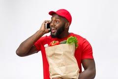 Leveringsconcept - Portret van de Knappe Afrikaanse Amerikaanse leveringsmens of koerier met kruidenierswinkel pakket en het spre stock foto's