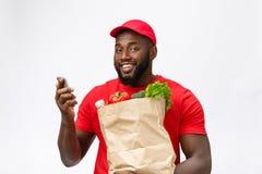 Leveringsconcept - Portret van de Knappe Afrikaanse Amerikaanse leveringsmens of koerier met kruidenierswinkel pakket en het spre stock afbeeldingen