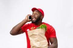 Leveringsconcept - Portret van de Knappe Afrikaanse Amerikaanse leveringsmens of koerier met kruidenierswinkel pakket en het spre stock foto