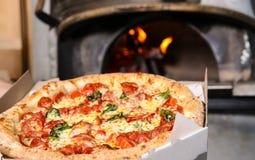 Leveringsdoos met smakelijke Italiaanse pizza dichtbij oven in restaurant royalty-vrije stock afbeeldingen