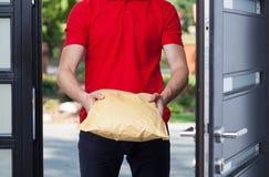 Leveringsmens die een pakket geven stock foto