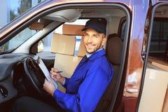 Leveringsmens die lijst met pakketten controleren stock fotografie