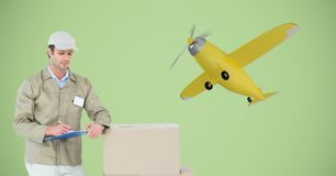 Leveringsmens die op klembord door pakket tegen 3d vliegtuig schrijven Royalty-vrije Stock Foto's