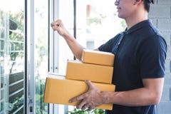 Leveringsmens die zich met pakketten in handen bevinden die in openlucht huiseigenaar open deur, de thuisbezorgingsdienst en het  stock foto