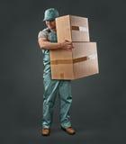Leveringsmens in groene eenvormige holding een doos Royalty-vrije Stock Afbeeldingen