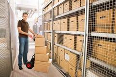 Leveringsmens met dozen op handvrachtwagen in pakhuis Stock Fotografie
