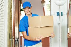 Leveringsmens met pakketdoos binnen Stock Foto