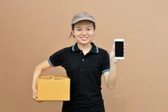 Leveringsvrouw die mobiele telefoon met kartondoos tonen Stock Afbeeldingen