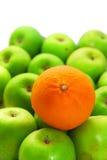 Levi in piedi fuori dalla folla con l'arancio e le mele Immagini Stock Libere da Diritti