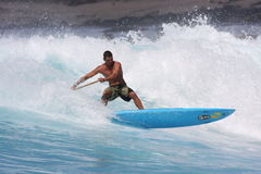 Levi in piedi in su la pala che pratica il surfing l'Hawai immagine stock