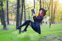 Levitación: la bruja lee un libro que cuelga sobre la tierra, ho Fotos de archivo libres de regalías