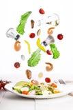 Levitatie van Heerlijke smakelijke plantaardige salade met zeevruchten op een witte plaat Stock Foto