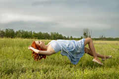 Levitating girl fly above the ground. Girl's dream of a flight Royalty Free Stock Photo