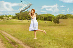 Levitating girl with umbrella flying above the ground. Royalty Free Stock Photography