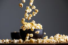Levitating popcorn around a ceramic bowl. Appetizing still life Stock Photos