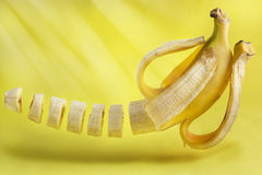 Levitating sliced banana on a yellow background. Stock Photography