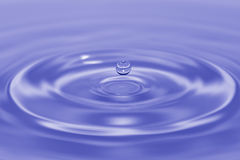 Levitation Blue. A drop of water as it splashes back up in blue and white duotone Royalty Free Stock Image