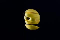 Levitation geschnittener Apfel mit schwarzem Hintergrund Lizenzfreie Stockbilder
