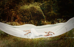 Levitation girl on the white cloth Royalty Free Stock Image