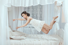 Levitation over the bed. Tender girl stretching her hands levitates above the bed Royalty Free Stock Photo