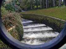LEVY OF WATER FLOWING FAST IN PARK. LEVY, MANMADE, WATERWAY, PARK, TREEES, WATER, FAST, FLOWING, SURF, METAL, IVY,GRASS, TRUNKS, BUSHES, LEVELS, STEPS, CURVE Stock Images