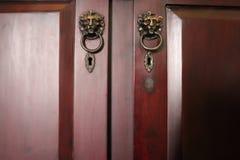 Lew kierownicze drzwiowe rękojeści, dwa bliźniaczego drewnianego drzwi kluczowa dziura, fotografia royalty free