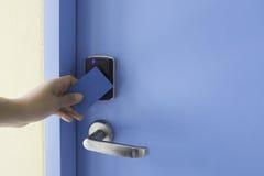 Lewa ręka chwyta kluczowej karty dotyk na elektronicznym ochraniacza kędziorka dostępie cont Zdjęcie Royalty Free