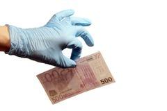 Lewa ręka mężczyzna w rękawiczki błękitnych gumowych chwytach pięćset euro z dwa palcami Pojęcie korupcja w medycynie, sc obrazy stock