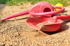 Lewe dziecko zabawki na piasku Czerwona podlewanie puszka, łopata i kolor żółty piłka, zdjęcie stock