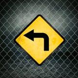 Lewego kierunku Grunge Żółty znak ostrzegawczy na Chainlink ogrodzeniu Obrazy Stock