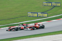 Lewis Hamilton pushed by Fernando Alonso. SEPANG, MALAYSIA - APRIL 10 : Lewis Hamilton pushed by Fernando Alonso at PETRONAS Malaysia Grand Prix on April 10 Royalty Free Stock Photos