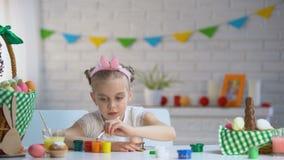 Leworęczna dziewczyna szczotkuje Wielkanocnych jajka z farbą, twórczość, dziecko hobby zdjęcie wideo