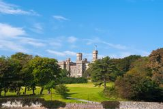 Lews Castle on estate landscape in Stornoway, United Kingdom. Castle with green grounds on blue sky. Victorian style. Architecture and design. Landmark and royalty free stock photos