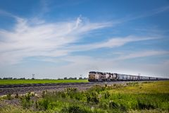 Freight train across the plains. LEXINGTON, NEBRASKA, JUNE 12, 2013 Union Pacific locomotives haul grain in covered hopper cars east of Lexington, Nebraska Royalty Free Stock Images