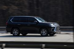 Lexus LX 570 black rides on the road. Against a background of blurred trees Stock Photography