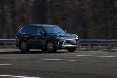 Lexus LX 570 black rides on the road. Against a background of blurred trees royalty free stock photo