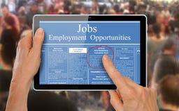 Leyendo anuncios del trabajo en línea en una tableta del ordenador - Foto de archivo libre de regalías