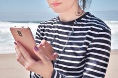 Leyendo en smartphone en la playa, día de verano fotografía de archivo