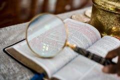 Leyendo la biblia con los vidrios de lectura y magnifique el 3:16 de cristal de Juan Fotos de archivo libres de regalías
