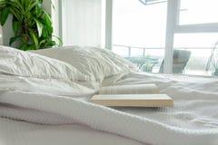 Lezend in bed, die in bed blijven Gerimpelde bladen in een gebruikt bed, in een echte huisslaapkamer Flatvensters die een balkon  stock afbeelding