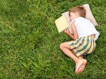 Lezend het boek openlucht Het slapen op het gras Intellectuele activiteiten stock afbeelding